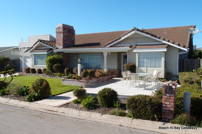 This beautiful home has beautiful landscaping and a front patio area.
